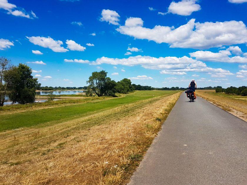 Mit dem Fahrrad auf dem Deich neben der Elbe